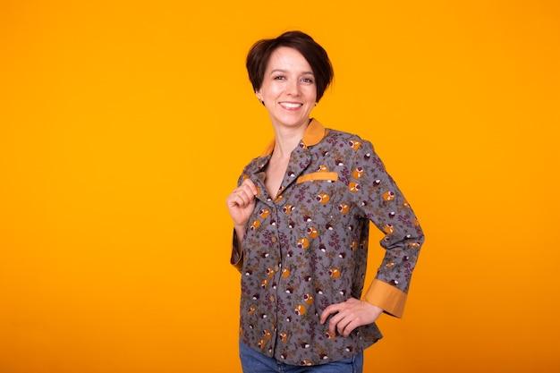 Aufgeregte frau im haus tragen pyjama, das auf gelb lächelt