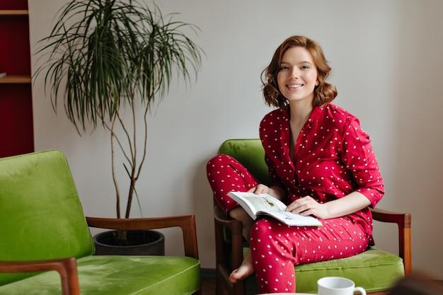 Aufgeregte frau im pyjama, die im sessel sitzt und kamera betrachtet. innenaufnahme der glücklichen frau, die buch hält.