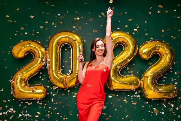 Aufgeregte frau im roten kleid hält ein glas champagner neujahrsfeier feiertagsparty konzept