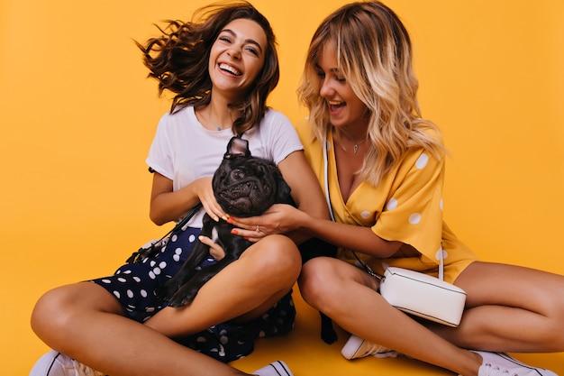 Aufgeregte frau im schwarzen rock, der mit ihrem welpen aufwirft. raffinierte schwestern sitzen auf leuchtendem gelb, während sie mit der französischen bulldogge spielen.