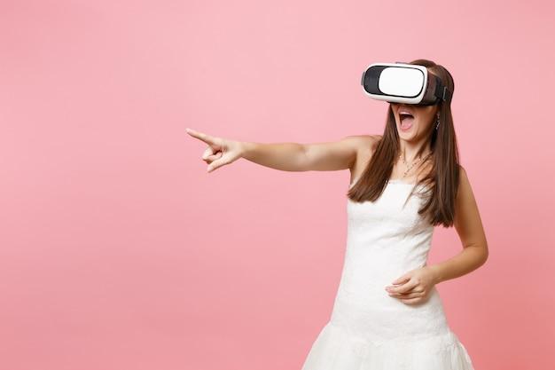 Aufgeregte frau im weißen kleid, headset der virtuellen realität, zeigefinger zur seite zeigend