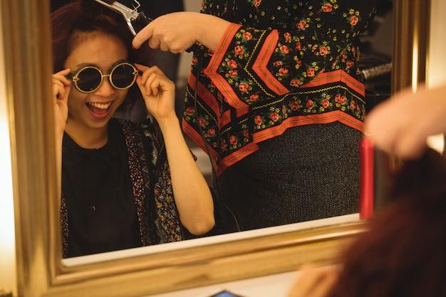 Aufgeregte frau in der sonnenbrille, die ihr haar erledigt erhält