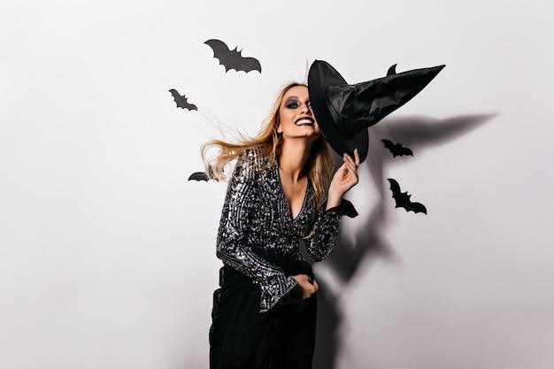 Aufgeregte frau in funkelnder kleidung, die auf halloween-party kühlt. inspiriertes blondes mädchen, das großen schwarzen hut hält.