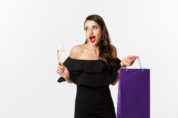 Aufgeregte frau kauft und trinkt champagner, hält einkaufstasche, sieht erstaunt aus und steht vor weißem hintergrund