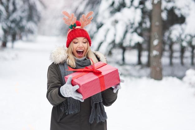 Aufgeregte frau mit großem weihnachtsgeschenk