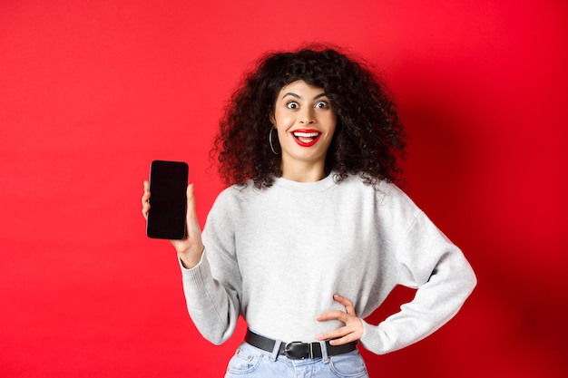 Aufgeregte frau mit lockigem haar und roten lippen, die einen leeren smartphone-bildschirm zeigt und vor freude schreit, auf rotem hintergrund stehend.