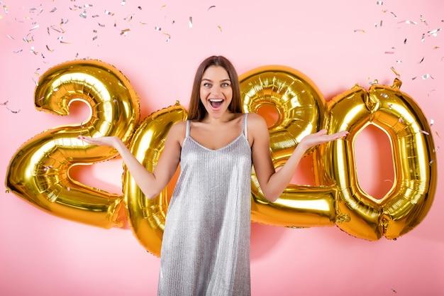Aufgeregte frau mit silbernem konfetti und goldenen 2020 ballonen des neuen jahres lokalisiert über rosa