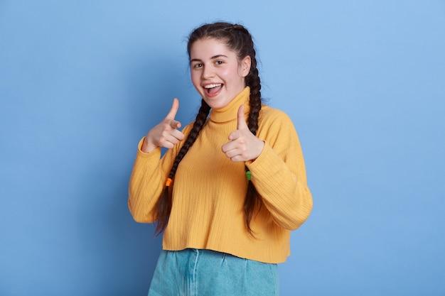 Aufgeregte frau mit zöpfen, die mit zeigefingern zeigen, mit charmantem lächeln schauend, hat positive emotionen, steht isoliert.