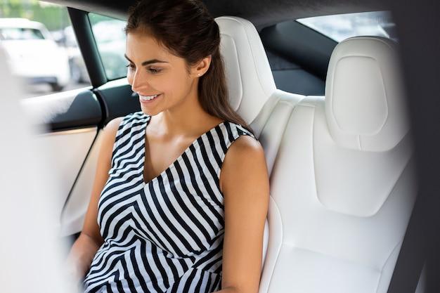 Aufgeregte frau. schöne junge geschäftsfrau, die auf dem rücksitz sitzt und sich motiviert und aufgeregt fühlt
