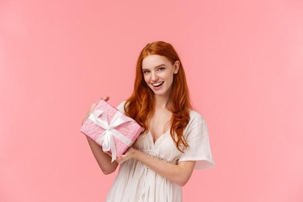Aufgeregte freche schöne rothaarigefrau im stilvollen weißen kleid, halten eingewickeltes geschenk und fragen vermutung, was nach innen ist und lächeln frech und geben romantisches geschenk für valentinstag, rosa wand
