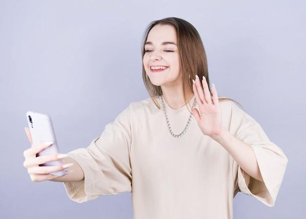 Aufgeregte freudige junge brünette frau im einfachen beigen trägershirt stehend, das selfie auf handy winkend handgruß lokalisiert auf lila farbiger wand, porträt macht