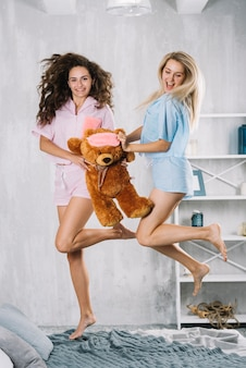 Aufgeregte freundinnen mit dem springen über bett mit weichem spielzeug