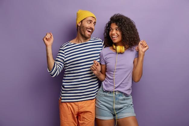 Aufgeregte fröhliche frau und mann tanzen, genießen lieblingsmusik, in freizeitkleidung gekleidet, schauen sich mit einem lächeln an, frau trägt kopfhörer um den hals