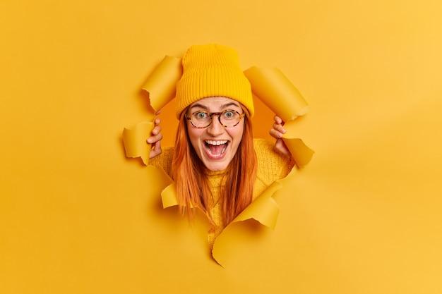 Aufgeregte fröhliche rothaarige tausendjährige frau starrt überraschend hat überglücklichen ausdruck hält mund offen trägt trendige helle hut transparente brille.