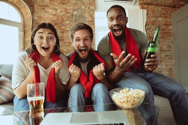 Aufgeregte fußballfans, die zu hause sportspiele verfolgen, fernunterstützung der lieblingsmannschaft während des ausbruchs der coronavirus-pandemie
