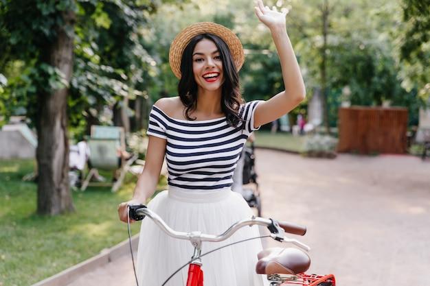 Aufgeregte gebräunte dame, die glückliche gefühle am sommerwochenende ausdrückt. spektakuläre junge frau mit fahrrad, das draußen kühlt.