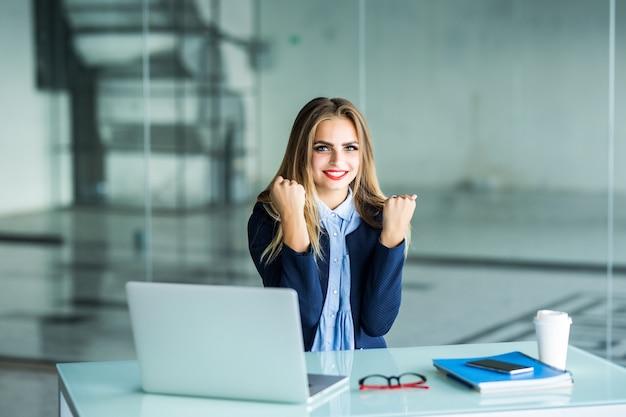 Aufgeregte geschäftsfrau, die nach dem erfolg das lesen eines smartphones gewinnt, das in einem desktop im büro sitzt
