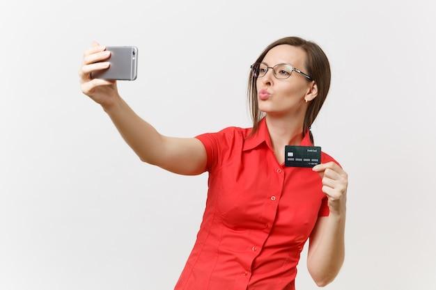 Aufgeregte geschäftsfrau im roten hemd, die selfie auf dem handy mit kreditkarte, bargeldlosem geld einzeln auf weißem hintergrund erschossen. bildungsunterricht im hochschulkonzept.