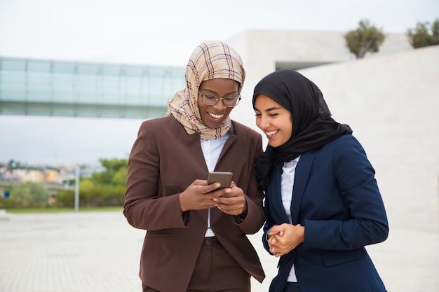 Aufgeregte glückliche büroangestellte, die smartphone betrachten