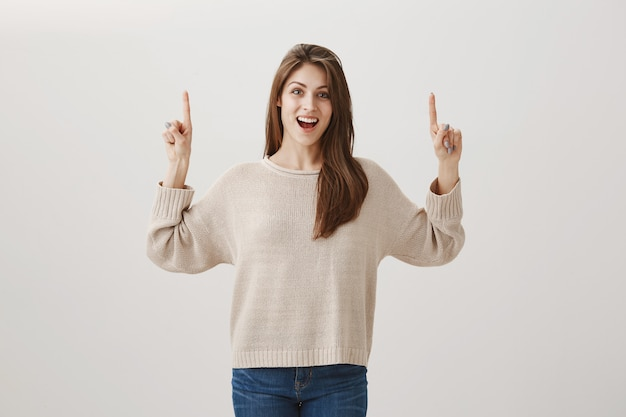 Aufgeregte glückliche frau, die promo mit erfreutem lächeln zeigt und finger nach oben zeigt