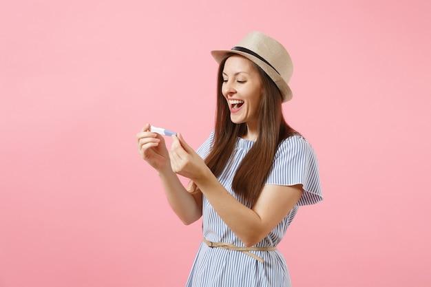 Aufgeregte glückliche frau im blauen kleid, hut in der hand halten, schwangerschaftstest einzeln auf rosafarbenem hintergrund betrachtend. medizinisches gesundheitswesen gynäkologisch, konzept der schwangerschaftsfruchtbarkeit mutterschaft menschen. platz kopieren.