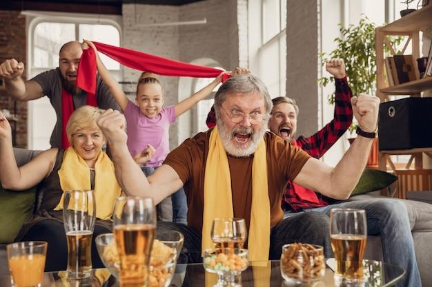 Aufgeregte, glückliche große familie, die fußball, fußball, basketball, hockey, tennis, rugbyspiel auf der couch zu hause sieht. fans jubeln emotional der lieblingsnationalmannschaft zu. sport, fernsehen, meisterschaft.