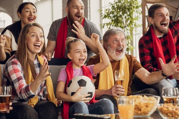 Aufgeregte, glückliche große familie, die fußball, fußballspiel auf der couch zu hause sieht. fans jubeln emotional der lieblingsnationalmannschaft zu. spaß haben von großeltern bis zu kindern. sport, fernsehen, meisterschaft.