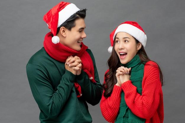 Aufgeregte glückliche junge asiatische paare, die bunte weihnachtsmotivkleidung tragen