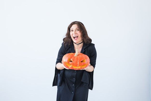 Aufgeregte glückliche junge frau im halloween-kostüm, das mit geschnitztem kürbis im lichtraum aufwirft.
