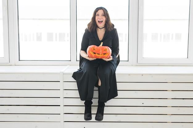 Aufgeregte glückliche junge frau im halloween-kostüm, die mit geschnitztem kürbis im lightroom aufwirft.