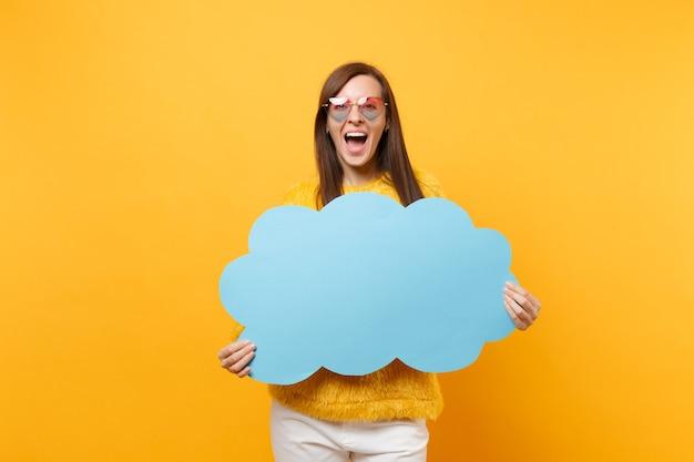 Aufgeregte glückliche junge frau in der herzbrille, die leeres leeres blau hält sagen sie wolke, sprechblase einzeln auf hellgelbem hintergrund. menschen aufrichtige emotionen, lifestyle-konzept. werbefläche.