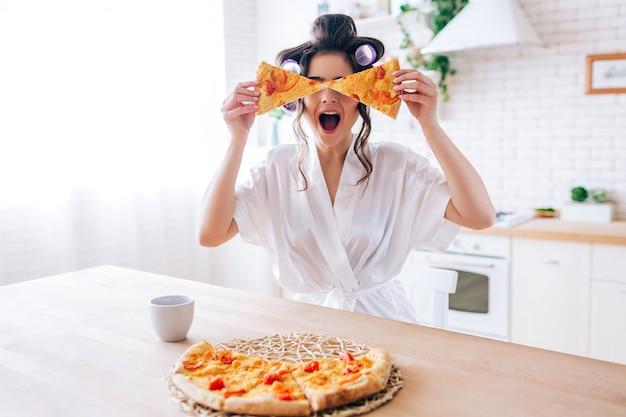 Aufgeregte glückliche junge frau in der küche mit pizzastücken plaing. bedecke die augen mit essen. sorglose haushälterin sehr verspielt. tragen sie einen weißen bademantel. unvorsichtige hausfrau.