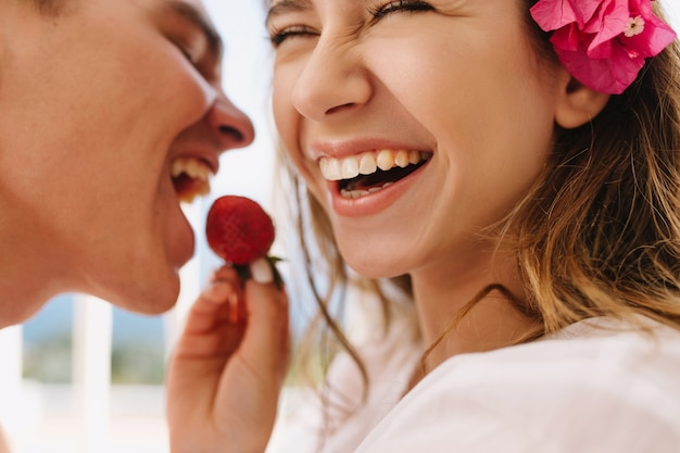 Aufgeregte glückliche junge frau mit niedlicher rosa blume im hellbraunen haar, das ihren lachenden ehemann mit frischer erdbeere füttert. nahaufnahmeporträt des romantischen genießens der flitterwochen und des essens von beeren