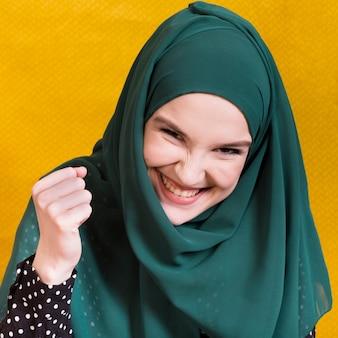 Aufgeregte glückliche moslemische junge frau, die kamera vor gelbem hintergrund betrachtet