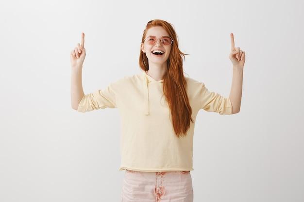 Aufgeregte glückliche rothaarige frau in der sonnenbrille, die freudig die finger nach oben zeigt