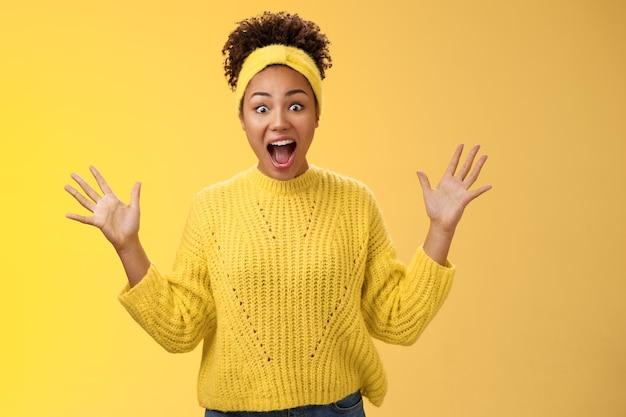 Aufgeregte glückliche, stilvolle afrikanische frau im pullover, die begeistert schreit, freudig gestikulierend erhobene palmen unglaubliches glück triumphiert, erhält extrem gute perfekte nachrichten, gewinnt im lotto, gelber hintergrund.