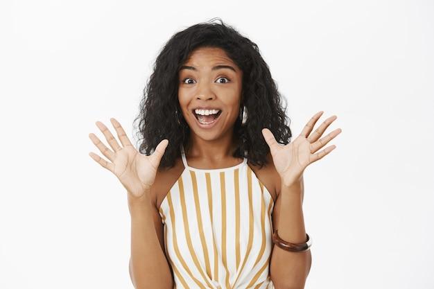 Aufgeregte glückliche und ausdrucksstarke attraktive afroamerikanerin mit lockiger frisur, die palmen anhebt