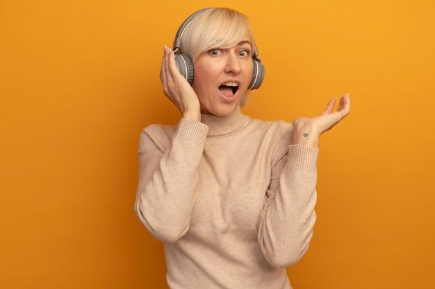 Aufgeregte hübsche blonde slawische frau auf kopfhörern steht hand offen auf orange