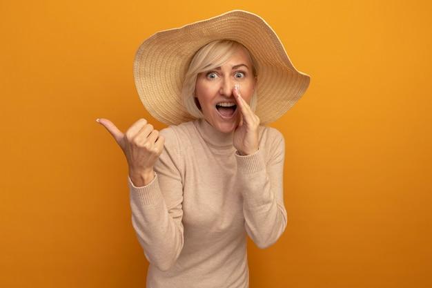 Aufgeregte hübsche blonde slawische frau mit strandhut hält hand nahe zum mund und zeigt zur seite auf orange