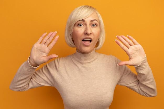 Aufgeregte hübsche blonde slawische frau steht mit erhobenen händen auf orange