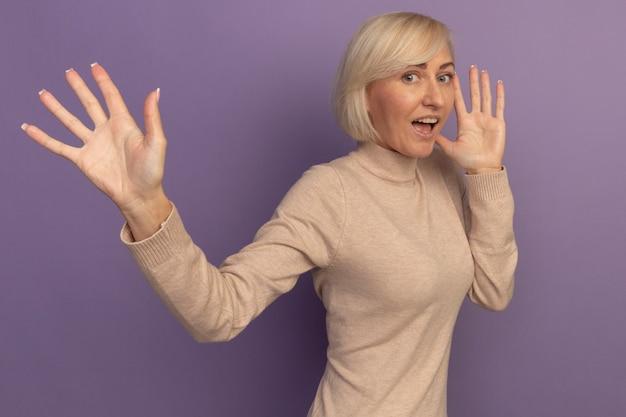 Aufgeregte hübsche blonde slawische frau steht seitlich mit erhobenen händen auf lila