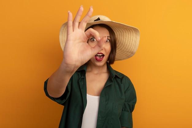 Aufgeregte hübsche frau mit strandhut gestikuliert ok handzeichen und schaut nach vorne durch finger isoliert auf orange wand