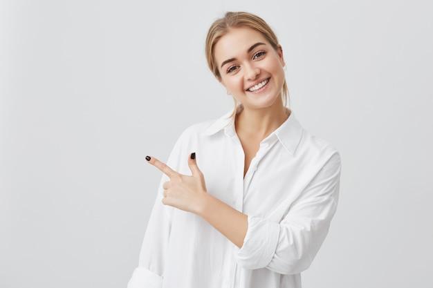 Aufgeregte hübsche junge blonde kaukasische frau, die weißes hemd trägt, das ihren zeigefinger zur seite zeigt, freudig mit ihren weißen zähnen lächelt und etwas überraschendes auf grauer kopienraumwand zeigt