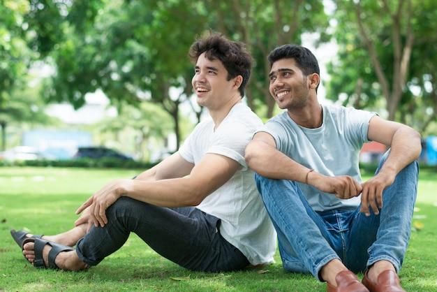 Aufgeregte hübsche junge männer in der freizeitbekleidung, die auf gras sitzt