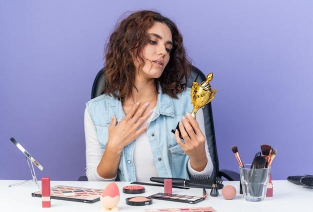 Aufgeregte hübsche kaukasische frau, die am tisch mit make-up-tools sitzt und den gewinnerpokal hält und betrachtet