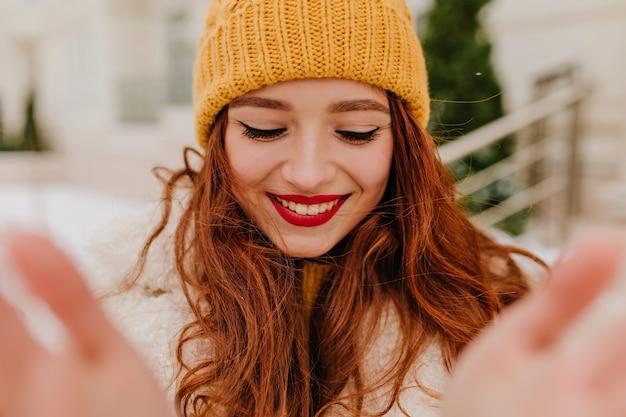 Aufgeregte ingwerfrau, die selfie im freien mit aufrichtigem lächeln macht. faszinierendes mädchen mit langen roten haaren, die winter genießen.