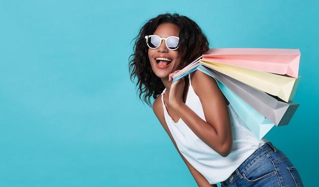 Aufgeregte junge afrikanerin, die einkaufstaschen hält