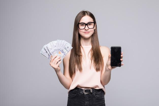 Aufgeregte junge amerikanische frau, die fan von dollarnoten und silberhandy lokalisiert über weißer wand hält