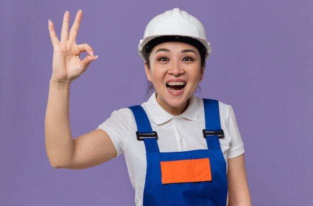 Aufgeregte junge asiatische baumeisterfrau mit weißem schutzhelm, die ok zeichen gestikuliert