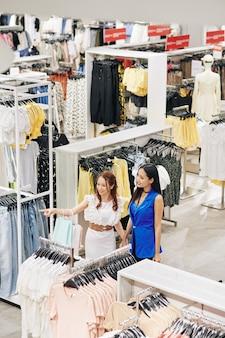 Aufgeregte junge asiatische frau, die hand des freundes hält und auf modeartikel auf kleiderständer im laden zeigt